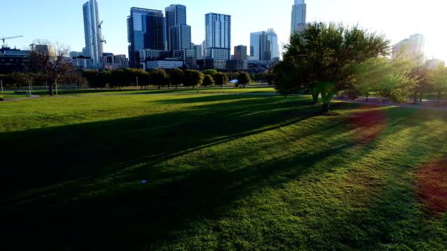 vídeos y material grabado en eventos de stock de sunbames entre árboles en el parque de butler en austin texas sunrise en el primer día de vistas aéreas por sur suroeste alrededor de la ciudad capital - parque ciudad