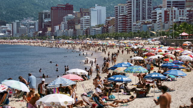 vidéos et rushes de sunbathers and swimmers crowd ipanema beach in rio de janeiro, brazil. - bain de soleil