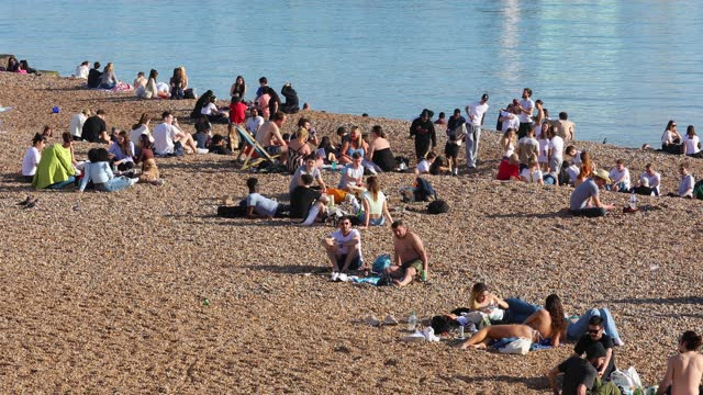 sunbathers enjoy the beach as a spell of hot weather coincides with lockdown restrictions being eased on march 30, 2021 in brighton, england.... - weather stock videos & royalty-free footage