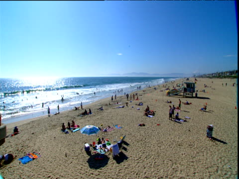 sunbathers relaxing on sandy beach lifeguard vehicle parked beside lifeguard station manhattan beach los angeles - cabina del guardaspiaggia video stock e b–roll