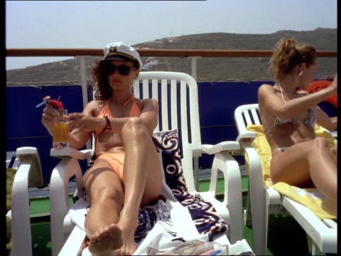 Sunbathers wearing sexy bikinis sip tropical drinks and lie in beach chairs on the deck of a sailboat.