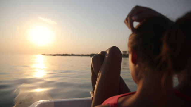 sunbathing at sunset is best for tanning. beautiful teenage girl relaxing on pedal boat - cross legged stock videos & royalty-free footage