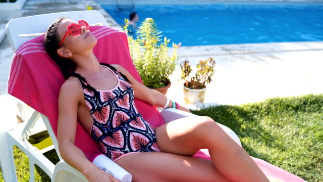 vídeos y material grabado en eventos de stock de tomar el sol por el lado de la piscina - bronceado