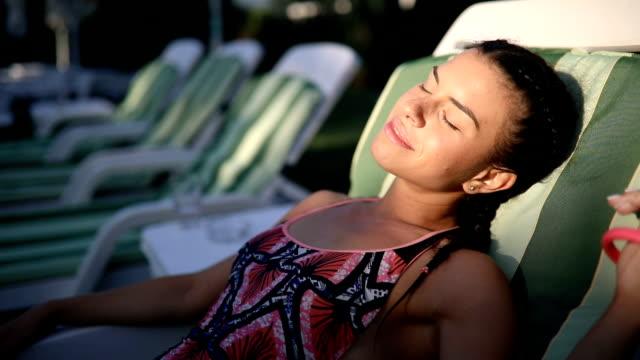 zum sonnenbaden mädchen genießen ihre zeit am pool - sonnenbaden stock-videos und b-roll-filmmaterial