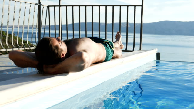 sunbathing on a pool side - infinity pool stock videos & royalty-free footage