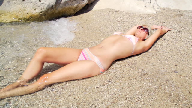 hd super slow mo: sunbathing on the beach - swimwear stock videos and b-roll footage