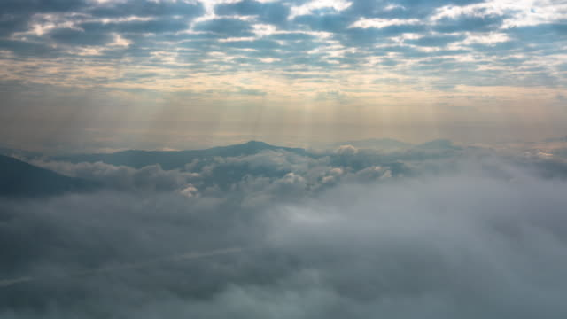 vídeos de stock e filmes b-roll de sunbeams and fog rolls across flowing over mountains - valley