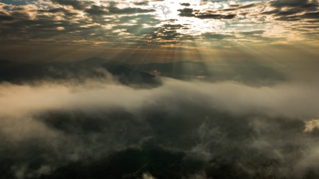 sunbeams and fog rolls across flowing over mountains - mountain range stock videos & royalty-free footage
