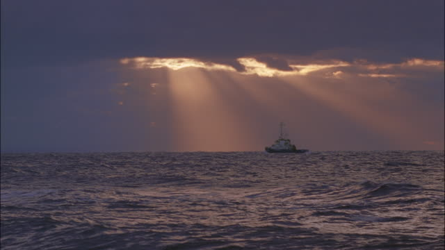 sunbeams filter through purple clouds onto a fishing boat below. - insel sylt stock-videos und b-roll-filmmaterial