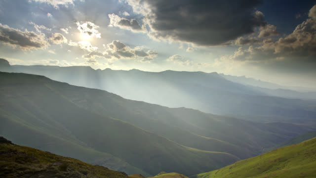 sunbeams filter through racing clouds as they drift over the drakensberg mountains in south africa. - 太陽光線点の映像素材/bロール