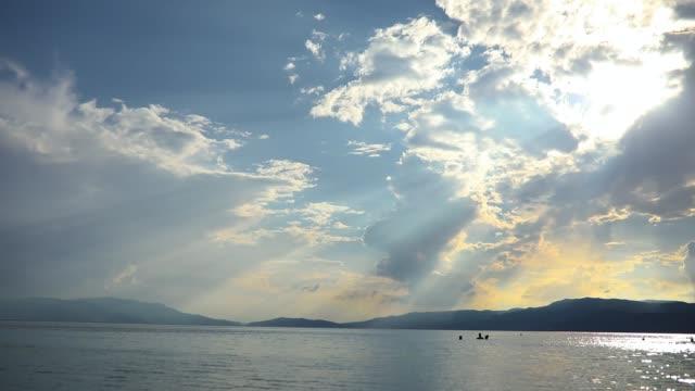 太陽光線は雲を通り抜けている。海の牧歌的光景。休暇、リラックス、水泳を楽しむ偶発的な人々 - 光線点の映像素材/bロール