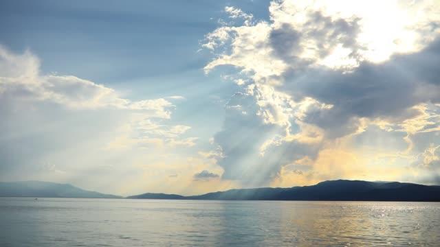 太陽光線は雲を通り抜けている。海の牧歌的光景。ギリシャビーチの静かな風景 - sunbeam点の映像素材/bロール