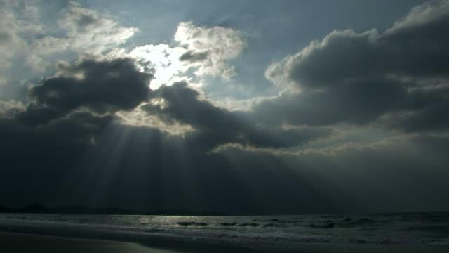 sunbeams pouring down through clouds over sea - 隠れる点の映像素材/bロール