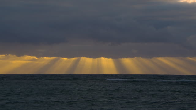 Sunbeams radiate from a bank of clouds over the ocean.