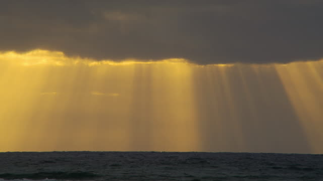 sunbeams radiate from a bank of clouds over the ocean. - concentric stock videos & royalty-free footage