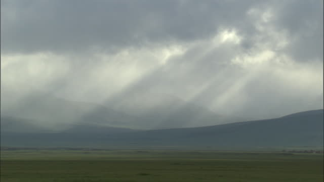 Sunbeams shine through black clouds over hills, Bayanbulak grasslands.
