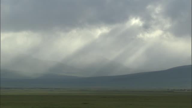 stockvideo's en b-roll-footage met sunbeams shine through black clouds over hills, bayanbulak grasslands. - steppe