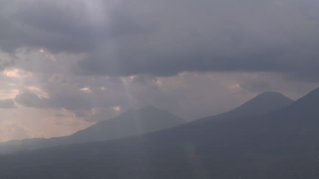 Sunbeams shine through swirling clouds above volcanic peaks. Available in HD.