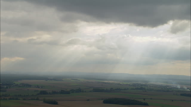 AERIAL WS Sunbeams shining down from clouds over landscape near Beaune / Cote de Beaune, France