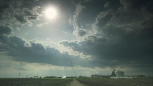 ws sunbeams shining down through clouds onto ethanol plant/ minnesota - ミネソタ州点の映像素材/bロール
