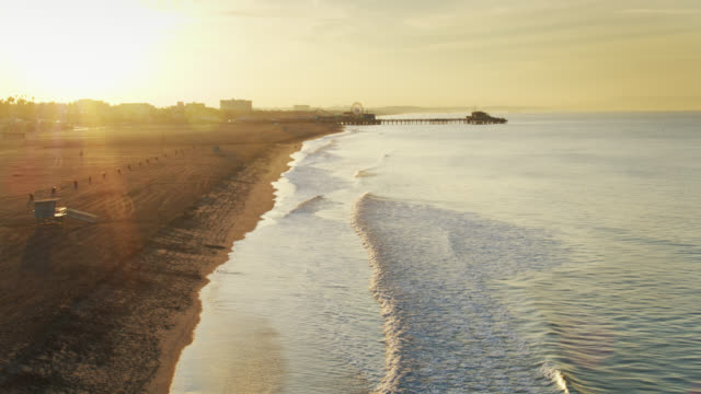 vídeos de stock e filmes b-roll de sunbeams shining on santa monica beach at dawn - drone shot - santa monica