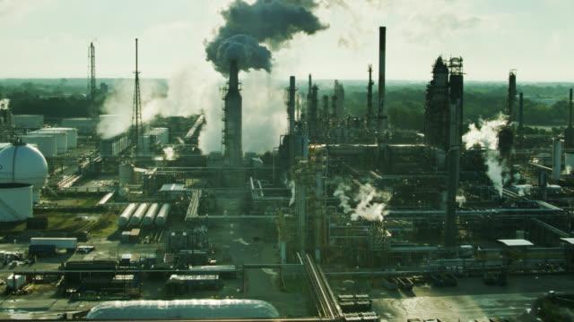 vídeos de stock, filmes e b-roll de sunbeams shining through structures of oil refinery in toledo, ohio - aerial - indústria petrolífera