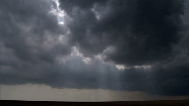 sunbeams shoot through dark storm clouds. - storm cloud stock-videos und b-roll-filmmaterial
