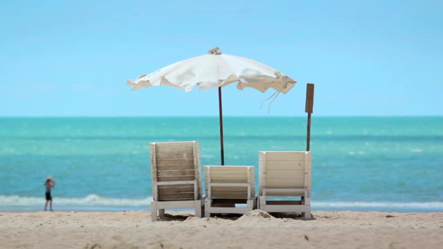sunbeds and umbrella on the beach - armchair stock videos & royalty-free footage