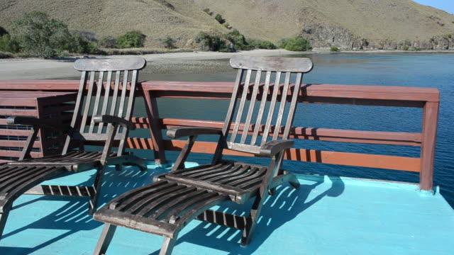 stockvideo's en b-roll-footage met sunbeds on the deck of a boat - voor anker gaan