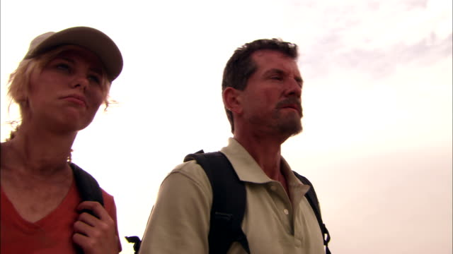 a sunburned couple talks as they hike down a dirt road in a desert. - survival stock videos & royalty-free footage