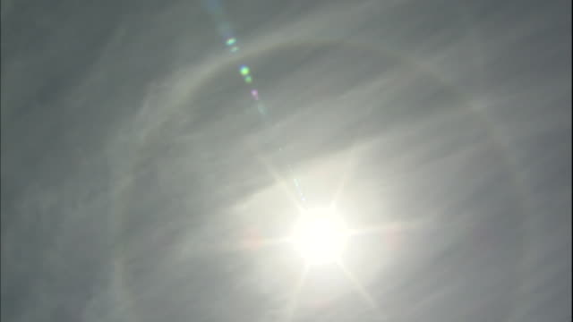 a sunburst glows inside a rainbow halo in a cloudy sky. - halo stock videos and b-roll footage