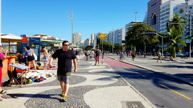 sunday in copacabana beach - zona pedonale strada transitabile video stock e b–roll
