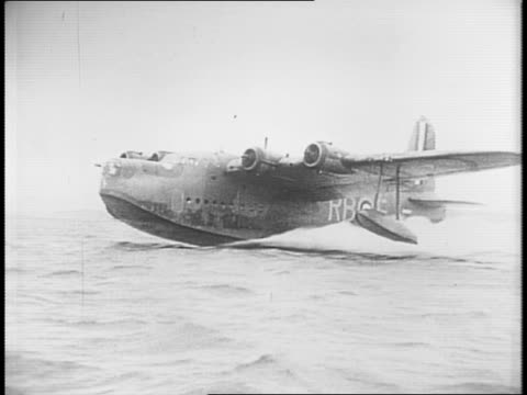 vidéos et rushes de sunderland flying boats in harbor / mechanics work on engine / bombs are loaded onto planes / plane taking off from water / cockpit with pilot /... - royal air force