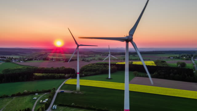 aerial: sundset above wind turbine - alternative energy stock videos and b-roll footage