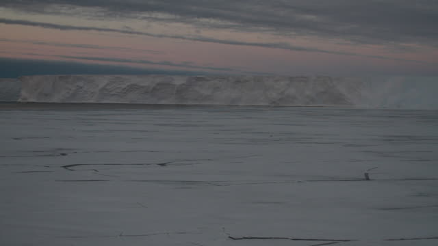 ws pan sunet over ice shelf with cracked ice - ice sheet stock videos and b-roll footage