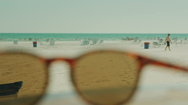 Sunglasses in foreground on the beach people in background