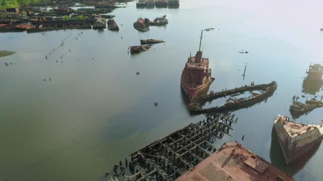 vidéos et rushes de navires abandonnés coulés et naufrages sur le cimetière de bateau dans le détroit de marée d'arthur kill à la rive de staten island, new york city, etats-unis. vidéo aérienne à basse altitude réalisée par le drone, avec le mouvement de la cam� - accident de transport