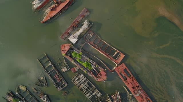 vidéos et rushes de navires abandonnés rouillés coulés sur le cimetière de bateau à staten island, new york city, etats-unis. en regardant vers le bas, directement au-dessus de la vidéo aérienne faite par le drone, avec le mouvement de la caméra panoramique. - bras de mer mer