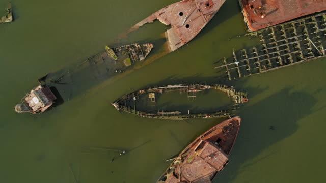 stockvideo's en b-roll-footage met tot zinken gebracht roestige verlaten schepen op de boat graveyard in staten island, new york city, usa. kijkend naar beneden, direct boven lucht video gemaakt door de drone, met de beweging van de draaiende camera. - scheepswrak
