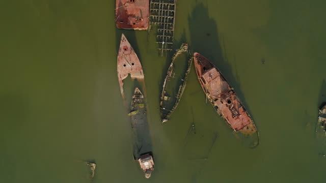 vídeos y material grabado en eventos de stock de barcos abandonados oxidados hundidos en el astillero boat graveyard en staten island, nueva york, ee. uu. mirando hacia abajo, directamente por encima del video aéreo hecho por el dron, con el movimiento de la cámara giratoria. - en ruinas