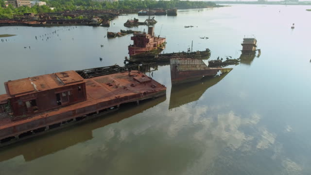 sunk rusty abandoned ships on the boat graveyard in staten island, new york city, usa. looking down, directly above aerial video made by the drone, with the panning camera motion. - shipwreck stock videos & royalty-free footage