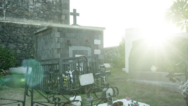 sunlight and memorials in saint paul marine cemetery, reunion - saint paul stock-videos und b-roll-filmmaterial