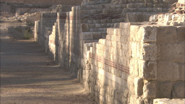Sunlight and shadows dapple ruined stone walls in Alexandria, Egypt.