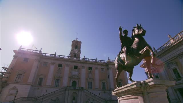 Sunlight beams behind Capitoline Museum at Piazza del Campidoglio near a statue of Marcus Aurelius in Rome.