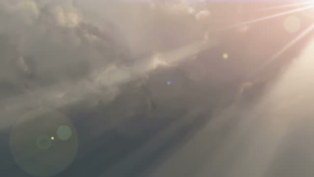sunlight beams through clouds (loop). - digital enhancement stock videos and b-roll footage