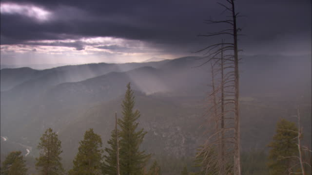 sunlight break through the clouds drifting over the yosemite national park. - yosemite stock videos and b-roll footage