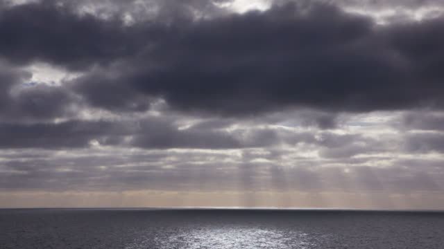 sunlight breaking over the ocean - storm cloud stock-videos und b-roll-filmmaterial