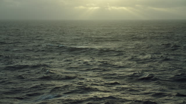 sunlight breaks through clouds over sea - orizzonte sull'acqua video stock e b–roll