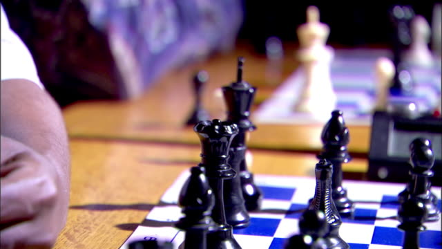 sunlight drenched chess board set up for game, black male hand moving white pawn & pressing top button of chess clock timer, black male hand moving... - drenched stock videos & royalty-free footage