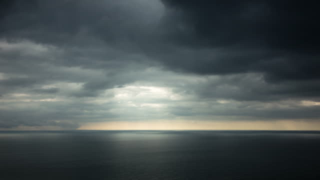 Sunlight fades over the horizon as dark stormy clouds pass over a calm English Channel